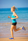 Woman running on the beach — Stock Photo