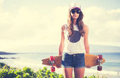 Hipster girl with skate board — Stock Photo