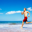 Athletic Man Running on Beach — Stock Photo