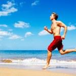 Athletic Man Running on Beach — Stock Photo