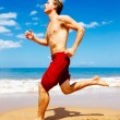 Athletic Man Running on Beach — Stock Photo #43700743