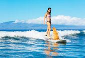 Mujer joven con su perro de surf — Foto de Stock