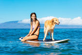 Young Woman Surfing with Her Dog — Stockfoto
