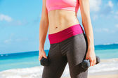 Torso of fitness woman holding barbells — Stock Photo