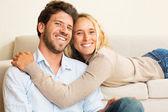 Coppia giovane felice a casa sul divano — Foto Stock
