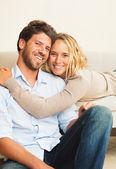 Joven pareja feliz en casa en sofá — Foto de Stock