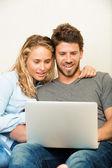 молодая пара на дому с использованием ноутбука — Стоковое фото