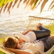 Couple relaxing in tropical hammock — Stock Photo #47044221