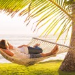 Couple relaxing in tropical hammock — Stock Photo