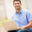 Young man working outside on laptop — Stock Photo #48790115
