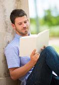 Man reading book outside — Stockfoto