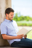 Man reading book outside — Stock Photo