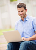 Man working outside on laptop — Stock Photo