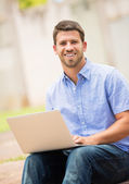 Young man working outside on laptop — Stock Photo