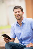 Young man reading E-book outside — Stock Photo