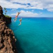 Friends cliff jumping into the ocean — Stock Photo #49705577