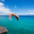 Woman doing backflip into ocean — Stock Photo #49705641