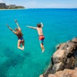 Friends cliff jumping into the ocean — Stock Photo #49705749