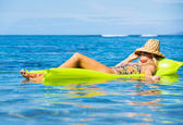 Young woman floating on raft — Stock Photo