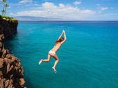 Woman jumping off cliff into the ocean — ストック写真