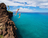 Friends cliff jumping into the ocean — Stockfoto