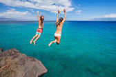 Friends cliff jumping into the ocean — 图库照片