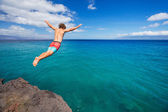 Man jumping off cliff into the ocean — 图库照片