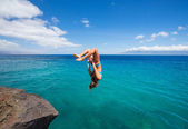 Woman doing backflip into ocean — Stock Photo