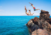 Friends cliff jumping into the ocean — Стоковое фото