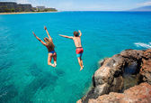 Friends cliff jumping into the ocean — Foto Stock