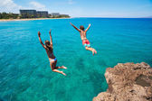 Friends cliff jumping into the ocean — Stok fotoğraf