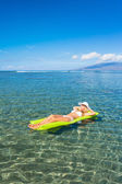 Woman floating on raft in tropical ocean — Stock Photo