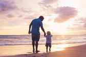 Father and son wallking on the beach — Stok fotoğraf