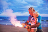Father and son lighting fireworks — Photo