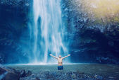Man in pool at the base of large waterfall — Stock Photo