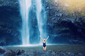 Woman in pool at base of large watefall — Stock Photo
