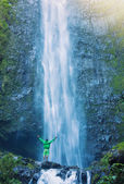 Man standing at base of massive waterfall — Photo