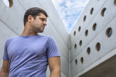 Man on the background of a modern concrete building — Stok fotoğraf