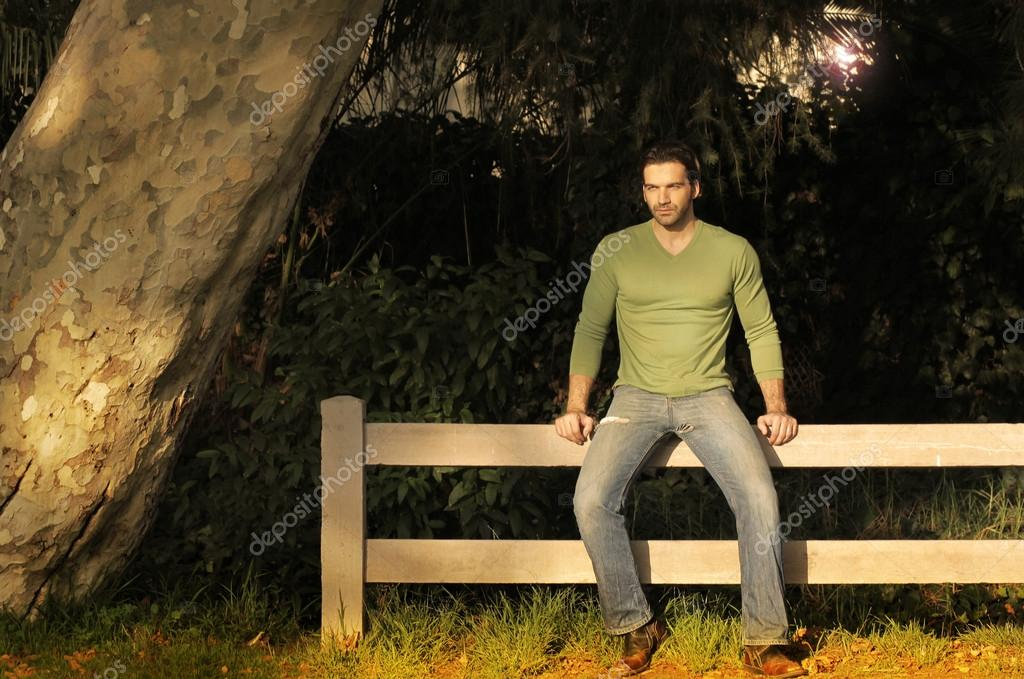 Young handsome man sitting on a rustic fence — Stock Photo #13184153