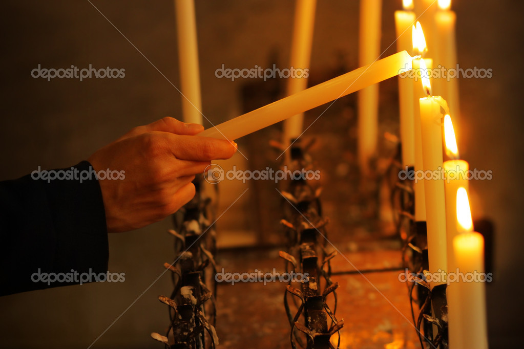Man's hand lighting candle with another candle in church — Stock Photo #14203553