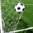 Soccer football in Goal net with green grass field — Foto de Stock