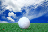 Pelota de golf en pasto contra el cielo azul y nubes blancas — Foto de Stock