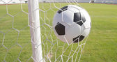 Soccer football in Goal net with green grass field  — Stock Photo