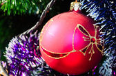 Red christmas ball with tinsel — Stock Photo