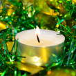 Candle with christmas tinsel — Stock Photo #13300390