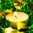 Candle with christmas tinsel — Stock Photo