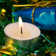 Candle with christmas green tinsel — Stock Photo