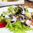 Greek salad on a table in a restaurant — Stock Photo #13407323