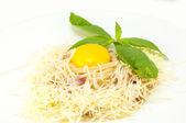 Spaghetti con formaggio e uova su un piatto bianco in un ristorante — Foto Stock