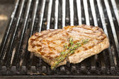 Cooking beef steak on a grill in the restaurant — Stock Photo